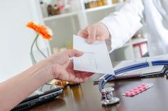Doctor que da una prescripción a su paciente Fotos de archivo libres de regalías