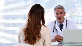 Doctor que discute con un paciente almacen de metraje de vídeo