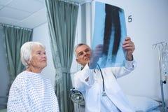 Doctor que discute informe de la radiografía con el paciente mayor Foto de archivo