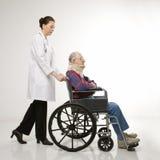 Doctor que empuja al paciente Foto de archivo libre de regalías