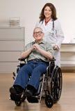 Doctor que empuja al paciente invalidado en silla de rueda Imagen de archivo libre de regalías