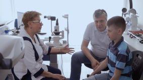 Doctor que escucha del padre y del hijo que se sienta en la oficina almacen de video