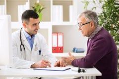 Doctor que escucha el paciente que explica el suyo doloroso Imagen de archivo