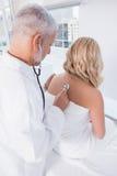 Doctor que escucha la respiración en su paciente Fotografía de archivo libre de regalías