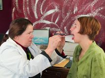 Doctor que estudia la garganta del paciente fotos de archivo libres de regalías