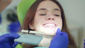 Doctor que examina blancura paciente de los dientes Dentista ascendente cercano que selecciona color almacen de video