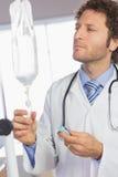 Doctor que examina el goteo intravenoso fotos de archivo