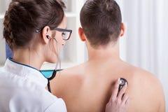 Doctor que examina los pulmones pacientes Fotos de archivo libres de regalías