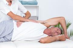 Doctor que examina su parte posterior del paciente Fotografía de archivo libre de regalías