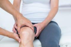 Doctor que examina su rodilla de los pacientes Imagenes de archivo