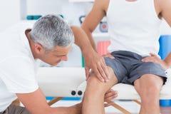 Doctor que examina su rodilla paciente Fotos de archivo