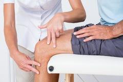 Doctor que examina su rodilla paciente Fotografía de archivo