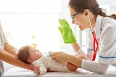 Doctor que examina a un bebé Fotos de archivo libres de regalías