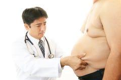 Doctor que examina una obesidad paciente Imagen de archivo