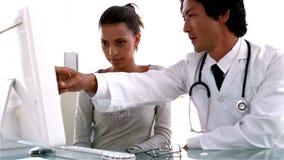 Doctor que explica algo en el ordenador al paciente almacen de metraje de vídeo