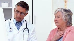 Doctor que explica algo a su paciente metrajes