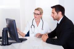 Doctor que explica algo a un paciente masculino foto de archivo libre de regalías