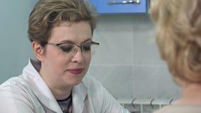Doctor que explica diagnosis a su paciente femenino almacen de metraje de vídeo