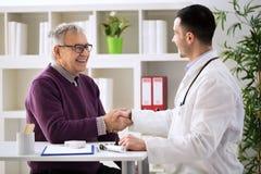 Doctor que felicita al paciente mayor en la recuperación Fotos de archivo libres de regalías