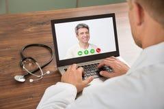 Doctor que habla con el paciente con la charla video Imagen de archivo