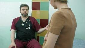Doctor que habla con la mujer embarazada almacen de metraje de vídeo