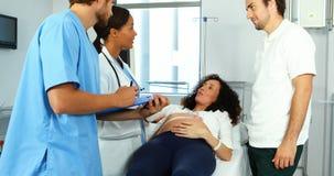 Doctor que habla con la mujer embarazada en sala almacen de video