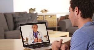 Doctor que habla con paciente en línea con el ordenador portátil Fotos de archivo libres de regalías