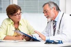 Doctor que habla con su paciente femenino imagenes de archivo