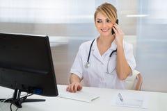 Doctor que habla en el teléfono móvil imagenes de archivo