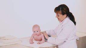Doctor que hace al bebé del masaje almacen de metraje de vídeo