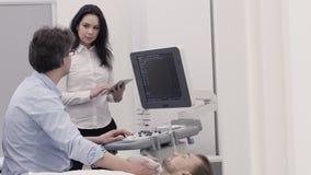 Doctor que hace diagnóstico del ultrasonido y la información fija de la enfermera en la tableta almacen de metraje de vídeo