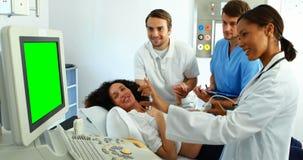 Doctor que hace la exploración del ultrasonido en mujer embarazada almacen de video