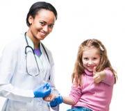 Doctor que hace la inyección vaccínea a un niño fotografía de archivo