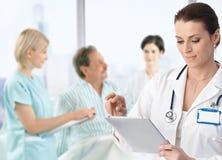 Doctor que hace notas en la cama de los pacientes Imagen de archivo