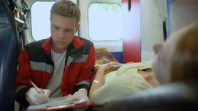 Doctor que hace preguntas pacientes y que rellena el impreso médico en ambulancia almacen de video