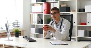 Doctor que lanza la manzana y que mira la cámara almacen de video