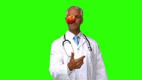 Doctor que lanza una manzana en la pantalla verde metrajes