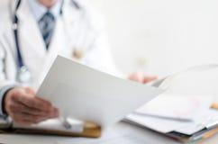 Doctor que lee notas médicas Foto de archivo libre de regalías