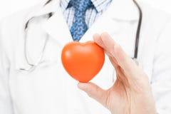 Doctor que lleva a cabo el corazón del juguete - concepto de la atención sanitaria Imágenes de archivo libres de regalías
