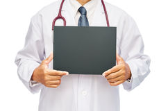 Doctor que lleva a cabo el tablero blanco en blanco de la bandera imagen de archivo libre de regalías