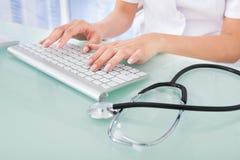 Doctor que mecanografía en el teclado de ordenador en clínica Foto de archivo libre de regalías