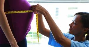 Doctor que mide el vientre de la mujer embarazada en sala almacen de metraje de vídeo