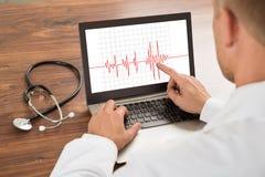 Doctor que mira el cardiograma del latido del corazón imagen de archivo