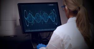 Doctor que mira la molécula de la DNA en el ordenador