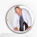Doctor que mira a través del tubo del escáner de MRI Imagen de archivo libre de regalías