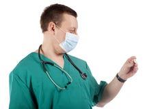 Doctor que mira un termómetro digital. Fotografía de archivo