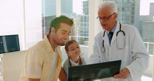 Doctor que muestra informe de la radiografía al paciente masculino metrajes
