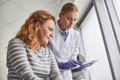 Doctor que muestra la imagen del bebé del ultrasonido a la madre futura fotografía de archivo
