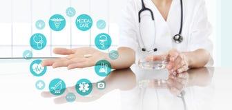 Doctor que muestra la medicina de la píldora con los iconos Atención sanitaria y médico imagen de archivo