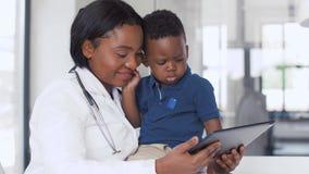 Doctor que muestra la PC de la tableta al paciente del bebé en la clínica almacen de metraje de vídeo